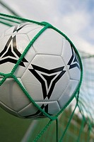 Close-up of a soccer ball in a goal post net