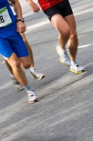 Low section view of three male athletes running on a running track