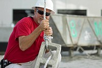 Male construction worker tightening a rope on a concrete block