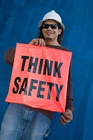 Young man holding a banner of think safety