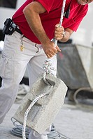Mid section view of a male construction worker pulling a concrete block
