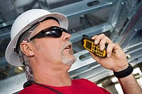 Close-up of a male construction worker talking on a walkie-talkie