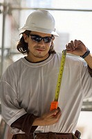 Young man holding a tape measure