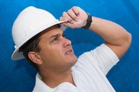 Close-up of a male construction worker adjusting his hardhat