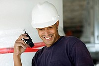 Close-up of a male construction worker talking on a walkie-talkie and smiling