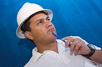 Close-up of a male construction worker holding a pen and thinking