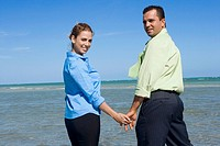 Portrait of a mid adult couple standing on the beach with holding their hands