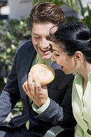 Businessman feeding a donut to a businesswoman smiling