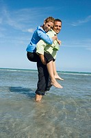Side profile of a mid adult woman riding piggyback on a mid adult man on the beach