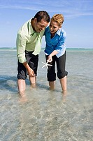 Mid adult couple playing with a starfish in water
