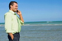 Side profile of a mid adult man talking on a mobile phone on the beach