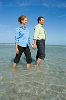 Mid adult couple wading on the beach with holding their hands