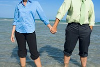 Mid section view of a mid adult couple standing on the beach with holding their hands
