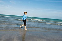 Side profile of a mid adult woman walking on the beach