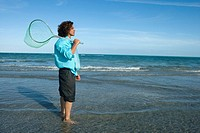 Side profile of a mid adult man holding a fishing net on the beach