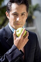 Portrait of a businessman eating a granny smith apple