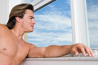 Close-up of a young man looking through a window