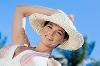 Portrait of a mid adult woman wearing a straw hat and smiling