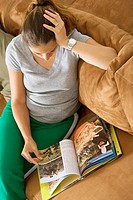 High angle view of a mid adult woman sitting on a couch and reading a book