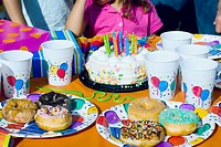 Birthday cake and donuts with presents on a table (thumbnail)
