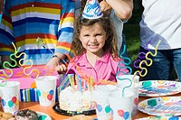 Portrait of a girl standing in front of a birthday cake