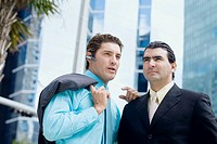 Businessman using a bluetooth device and another businessman standing in front of him