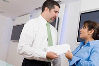 Businessman giving a document to a businesswoman