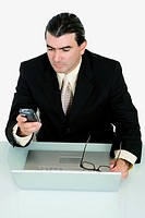 Businessman using a mobile phone in front of a laptop
