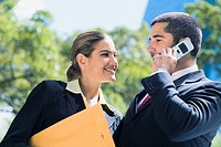 Businessman talking on a mobile phone with a businesswoman smiling beside him