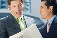 Businessman looking at a stock exchange report with another businessman standing beside him and smiling