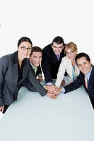 Portrait of two businesswomen and three businessmen placing their hands on each other