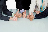 Five business executives showing thumbs up sign in a meeting