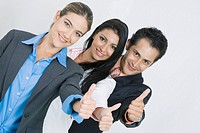 Portrait of two businesswomen and a businessman standing in a row and making a thumbs up sign