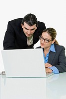 Businessman and a businesswoman using a laptop
