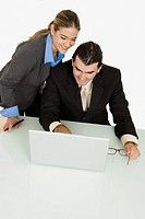 Businessman and a businesswoman using a laptop and smiling