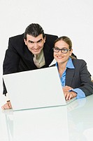 Portrait of a businessman and a businesswoman smiling in front of a laptop