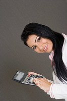 Portrait of a businesswoman holding a calculator and smiling