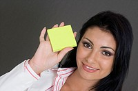 Portrait of a businesswoman holding a blank adhesive note and smiling