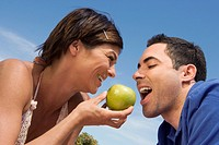 Mid adult woman feeding a green apple to a mid adult man