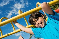 Portrait of a boy hanging on monkey bars and smiling
