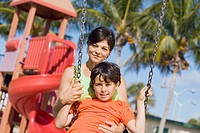 Portrait of a mid adult woman swinging on a swing with her son and smiling