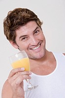 Portrait of a mid adult man holding a glass of orange juice