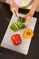 High angle view of a woman cutting a green bell pepper on a cutting board