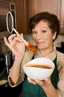Portrait of a senior woman holding a bowl of tomato soup and a wooden spoon in the kitchen