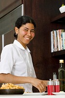 Portrait of a maid preparing food in the kitchen and smiling