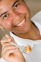 Portrait of a maid holding food in a fork and smiling