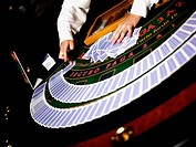 Close-up of a casino worker's hand arranging gambling chips on a gambling table