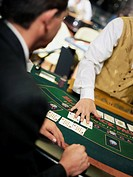 Mid section view of a casino worker dealing with playing cards on a gambling table