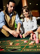Casino worker arranging gambling chips for a young woman in a casino