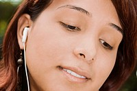 Close-up of a young woman listening to music